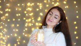 Frau in den Kopfhörern, die, hörend Musik, die Lichter betrachtend smilling sind, schließt ihre Augen und entspannt sich stock video footage