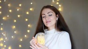 Frau in den Kopfhörern, die, hörend Musik, die Lichter betrachtend smilling sind, schließt ihre Augen und entspannt sich Hintergr stock footage