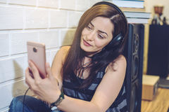 Frau in den Kopfhörern hörend auf ein audiobook an einem Telefon, das auf Wandhintergrund sitzt stockfotografie