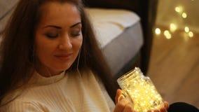 Frau in den Kopfhörern hört Musik, betrachtet die Lichter, schließt ihre Augen und entspannt sich stock footage