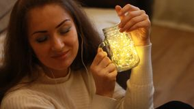 Frau in den Kopfhörern schließt ihre Augen, macht einen Wunsch und ein Träumen Hintergrund mit bokeh Leuchten stock video