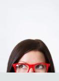 Frau in den rot-gestalteten Brillen, die weg schauen Lizenzfreie Stockfotos