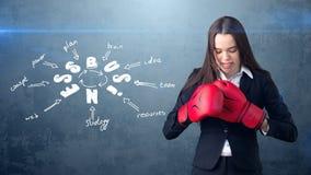 Frau in den roten Boxhandschuhen, welche die nahe Wand mit einer Geschäftsideenskizze gezeichnet auf sie stehen Konzept eines erf Lizenzfreie Stockfotos