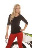 Frau in den roten Hosen, die Gläser vor Fahrrad halten stockfotografie