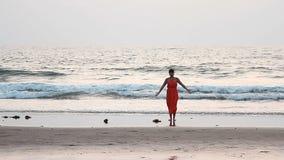 Frau in den roten Sarongen, die auf dem Strand im Sonnenuntergang sich entspannen, strahlt aus stock footage