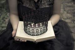 Frau in den schwarzen Kleiderholdings ein Buch und eine Krone Stockfoto