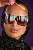 Frau in den Sonnenbrillen, die durch b schauen Stockbild