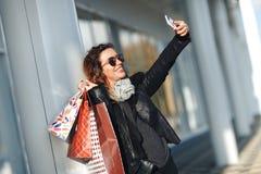 Frau in den Sonnenbrillen eine schwarze Lederjacke, schwarze Jeans, die ein Bündel Einkaufstaschen tun Selfie vor widergespiegelt Stockbilder