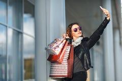 Frau in den Sonnenbrillen eine schwarze Lederjacke, schwarze Jeans, die ein Bündel Einkaufstaschen tun Selfie vor widergespiegelt Stockbild