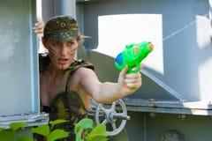 Frau in den Tarnungeintragfäden von einer Wasserpistole Lizenzfreie Stockfotografie