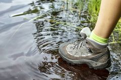 Frau in den touristischen wasserdichten Wanderstiefelwegen durch das Wasser in den Pfützen stockbilder