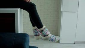 Frau in den warmen Socken, die auf dem Tisch auf der Küche sitzen stock video footage