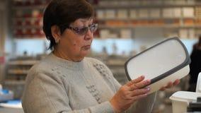 Frau in den Wertpapierkäufen des Berufshandels ein Plastikbehälter für Lebensmittel Lizenzfreie Stockfotografie