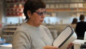 Frau in den Wertpapierkäufen des Berufshandels ein Plastikbehälter für Lebensmittel Lizenzfreies Stockfoto