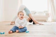 Frau in der abwärts Hundeposition während ihr Baby, das zu Hause spielt Lizenzfreie Stockbilder