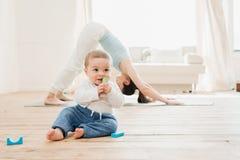 Frau in der abwärts Hundeposition während ihr Baby, das zu Hause spielt Stockbilder