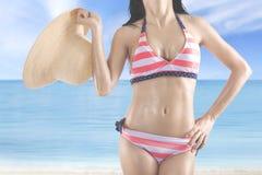 Frau in der Badebekleidung hält Hut am Ufer lizenzfreies stockfoto