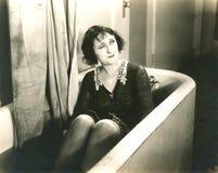 Frau in der Badewanne blinzeln völlig gekleidet Lizenzfreies Stockbild