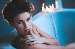 Frau in der Badewanne mit Kerzen stockfoto