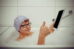 Frau in der Badewanne mit Tablet-Computern machen o.k. Stockfotos