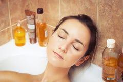 Frau in der Badewanne voll Schaumgummi Stockbild
