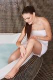 Frau in der Badezimmer-Sorgfalt über ihre perfekten Beine Stockbilder