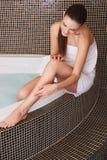 Frau in der Badezimmer-Sorgfalt über ihre perfekten Beine Lizenzfreie Stockbilder