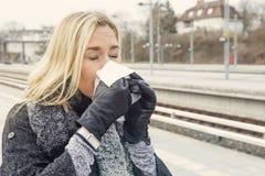 Frau an der Bahnstation, die eine Kälte hat Stockfotografie