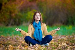 Frau in der beige Strickjacke, in den Blue Jeans und in der Schalmeditation Stockfoto