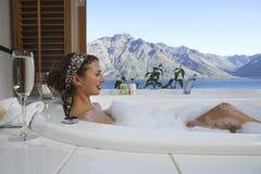 Frau in der Blasen-Badewanne mit Mountainsee außerhalb des Fensters Lizenzfreie Stockfotos