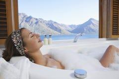 Frau in der Blasen-Badewanne mit Mountainsee außerhalb des Fensters Lizenzfreie Stockbilder