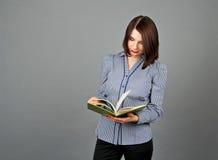 Frau in der blauer Blusenstellung und -lesung ihre Grünanmerkungen Lizenzfreies Stockfoto