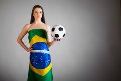 Frau in der brasilianischen Flagge und im Fußball Stockbilder