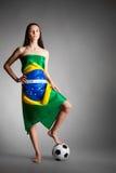 Frau in der brasilianischen Flagge und im Fußball Stockfotografie
