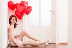 Frau in der Brautwäsche mit roten Ballonen Stockbild
