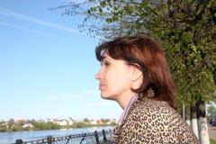 Frau der durchschnittlichen Jahre betrachtet den Fluss Stockbild
