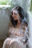 Frau in der Ecke mit Spinnennetzen Lizenzfreies Stockfoto