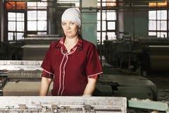 Frau an der Fabrik stockbilder