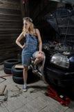 Frau in der Garage, die Auto repariert Stockfotografie