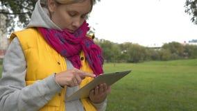 Frau in der gelben Weste unter Verwendung des Tabletten-PC im Park stock video footage