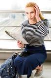 Frau in der gestreiften Bluse sitzend an der Station oder am Ende und die Karte betrachtend und seinen Kopf in der Überraschung h Lizenzfreies Stockfoto