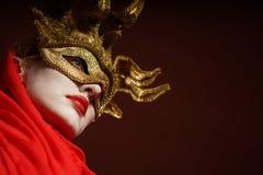 Frau in der goldenen Parteimaske Stockfotografie