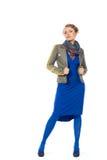 Frau in der grauen Jacke und im blauen Kleid zum Äußersten Stockfotos