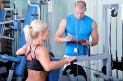 Frau in der Gymnastik mit persönlichem Kursleiter Lizenzfreies Stockbild