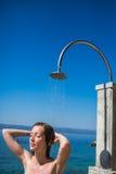 Frau der hübschen, jungen Frau unter Dusche auf dem Strand Lizenzfreies Stockbild