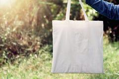Frau der Hand Baumwolle Tote Bag auf Hintergrund des grünen Grases halten stockfotos