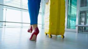 Frau in der hellen Kleidung rollt gelben Koffer im Flughafen