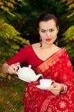 Frau in der indischen Sari mit Teekanne und Tasse Tee lizenzfreies stockfoto