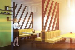 Frau in der Innenseitenansicht des gelben Sofarestaurants Lizenzfreie Stockbilder