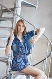 Frau in der Jeansjacke, die auf Treppe sitzt Stockfoto